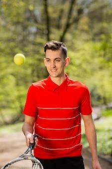 Mężczyzna w czerwonej koszulce pozuje z rakietą tenisową i piłką na tle zielonego parku.