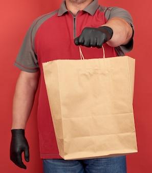 Mężczyzna w czerwonej koszulce, ubrany w czarne lateksowe rękawiczki, trzyma papierową torbę na zakupy