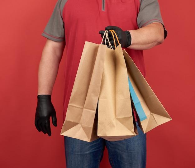 Mężczyzna w czerwonej koszulce, ubrany w czarne lateksowe rękawiczki, trzyma papierowe torby na zakupy