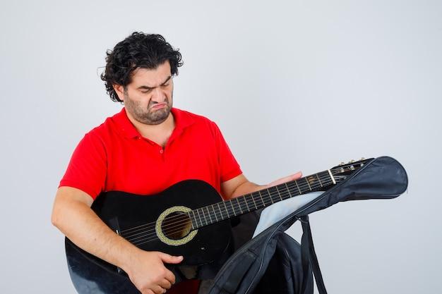 Mężczyzna w czerwonej koszulce wyjmuje gitarę z futerału i wygląda zamyślony