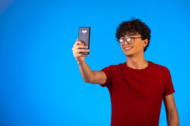 Mężczyzna w czerwonej koszuli, biorąc selfie lub telefon.