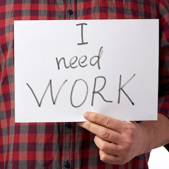 Mężczyzna w czerwonej koszuli i dżinsach trzyma kawałek papieru z napisem: potrzebuję pracy
