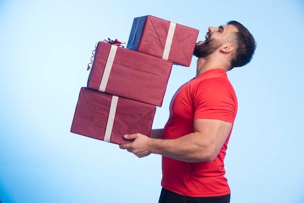 Mężczyzna w czerwonej koszuli posiada zapas pudełek prezentów.