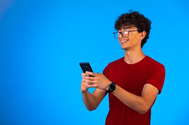 Mężczyzna w czerwonej koszuli przy selfie na smartfonie.