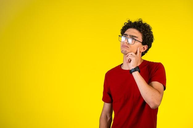 Mężczyzna w czerwonej koszuli przykłada rękę do piersi i myśli