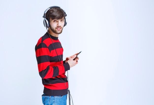 Mężczyzna w czerwonej koszuli w paski, słuchając słuchawek i ustawiając muzykę ze swojej listy odtwarzania na smartfonie.