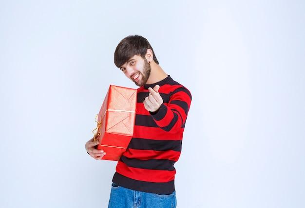 Mężczyzna w czerwonej koszuli w paski, trzymając czerwone pudełko i prosząc o zapłatę.