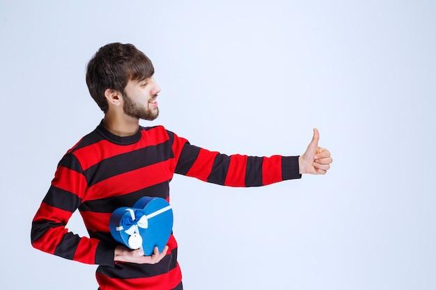 Mężczyzna w czerwonej koszuli w paski, trzymając pudełko upominkowe w kształcie niebieskiego serca i pokazując kciuk do góry.