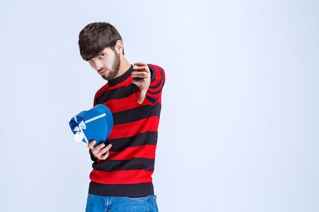 Mężczyzna w czerwonej koszuli w paski, trzymając pudełko w kształcie niebieskiego serca i pokazując znak niechęci.