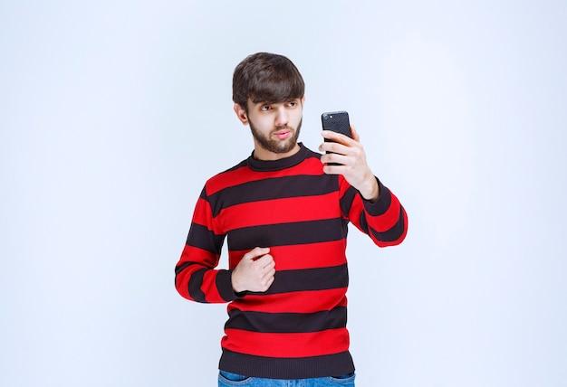 Mężczyzna w czerwonej koszuli w paski trzymający czarny smartfon i pokazujący, że lubi nowe funkcje.