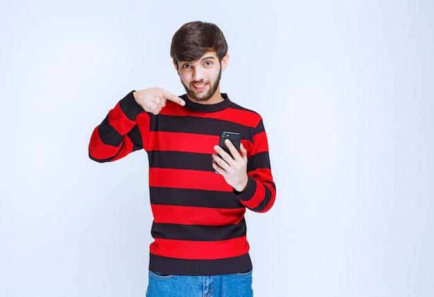 Mężczyzna w czerwonej koszuli w paski trzymający czarny smartfon i wskazujący na niego.