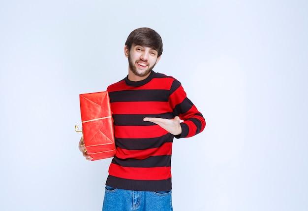 Mężczyzna w czerwonej koszuli w paski, trzymający czerwone pudełko i promujące go.