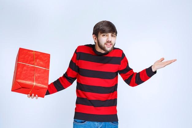 Mężczyzna w czerwonej koszuli w paski, trzymający czerwone pudełko i wygląda na zdezorientowanego i zamyślonego.