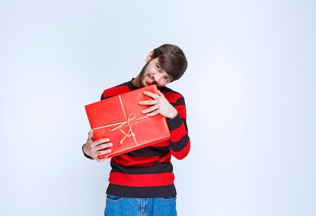 Mężczyzna w czerwonej koszuli w paski, trzymający czerwone pudełko upominkowe, dostarczający je i prezentujący