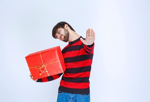 Mężczyzna w czerwonej koszuli w paski, trzymający czerwone pudełko upominkowe, mocno je przytulający i nie chcący się z nikim dzielić.