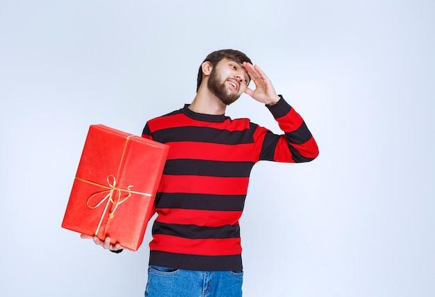 Mężczyzna w czerwonej koszuli w paski trzymający czerwone pudełko wygląda na zmęczonego i sennego.