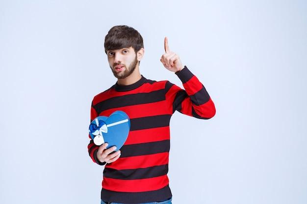 Mężczyzna w czerwonej koszuli w paski, trzymający pudełko w kształcie niebieskiego serca i wyglądający na zamyślony lub jakby miał dobry pomysł.