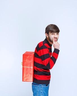 Mężczyzna w czerwonej koszuli w paski, ukrywając za sobą czerwone pudełko.