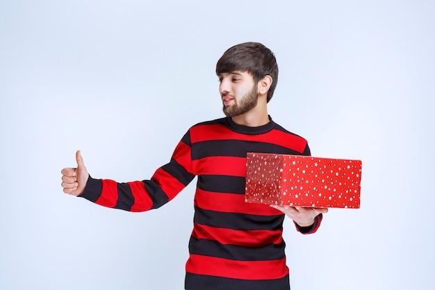 Mężczyzna w czerwonej koszuli w paski z czerwonym pudełkiem i pokazując znak przyjemności.