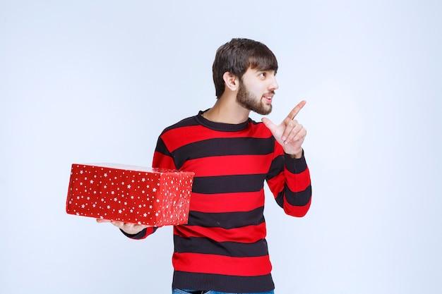 Mężczyzna w czerwonej koszuli w paski z czerwonym pudełkiem na prezenty i dzwoniący do kogoś, by go zaprezentować.