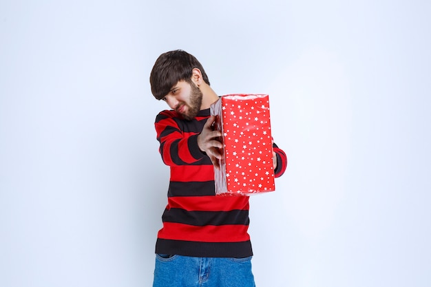 Mężczyzna w czerwonej koszuli w paski z czerwonym pudełkiem prezentowym i oferujący ją