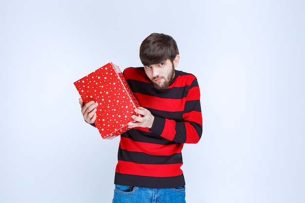 Mężczyzna W Czerwonej Koszuli W Paski Z Czerwonym Pudełkiem Prezentowym I Oferujący Ją Darmowe Zdjęcia