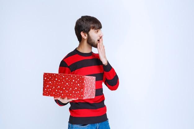 Mężczyzna w czerwonej koszuli w paski z czerwonym pudełkiem wygląda na przestraszonego i przestraszonego.