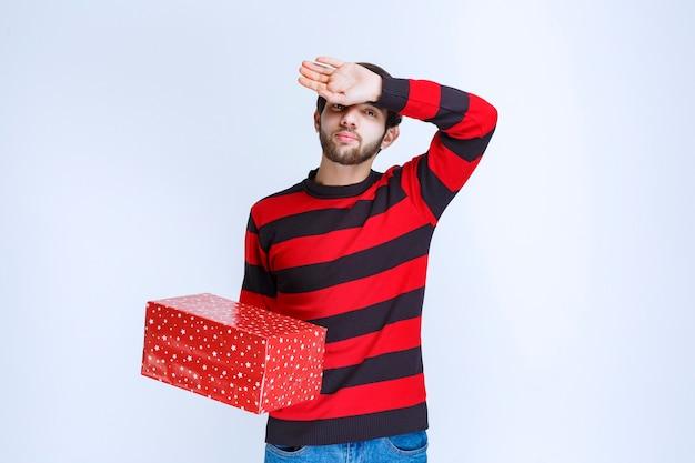 Mężczyzna w czerwonej koszuli w paski z czerwonym pudełkiem wygląda na sennego i wyczerpanego.