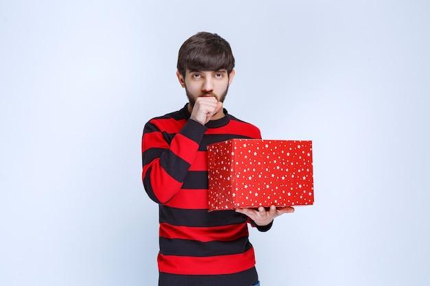 Mężczyzna w czerwonej koszuli w paski z czerwonym pudełkiem wygląda na zdezorientowanego i zamyślonego.