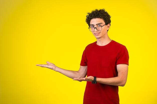 Mężczyzna w czerwonej koszuli wprowadza coś gestami dłoni.