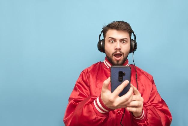 Mężczyzna w czerwonej kurtce i brodzie stoi na niebiesko ze słuchawkami i smartfonem w rękach