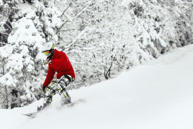 Mężczyzna w czerwonej kurtce narciarskiej i białym hełmie schodzi po zaśnieżonym wzgórzu w lesie