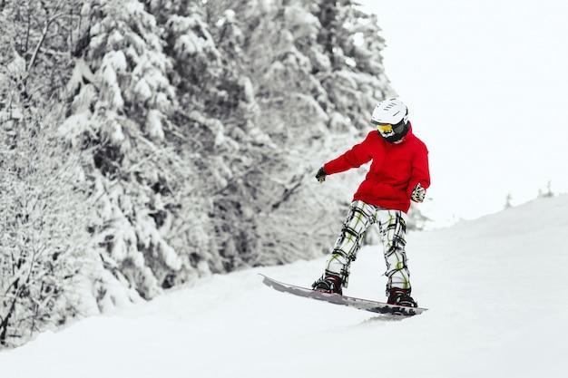 Mężczyzna w czerwonej kurtce narciarskiej schodzi ze wzgórza na snowboardzie