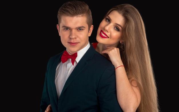 Mężczyzna w czerwonym krawacie i kobieta z czerwonymi ustami pozują