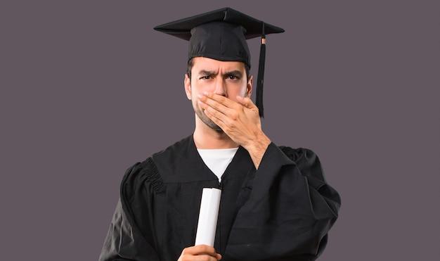 Mężczyzna w dniu jego ukończenia uniwersytet obejmuje usta rękami, mówiąc coś niedobrze