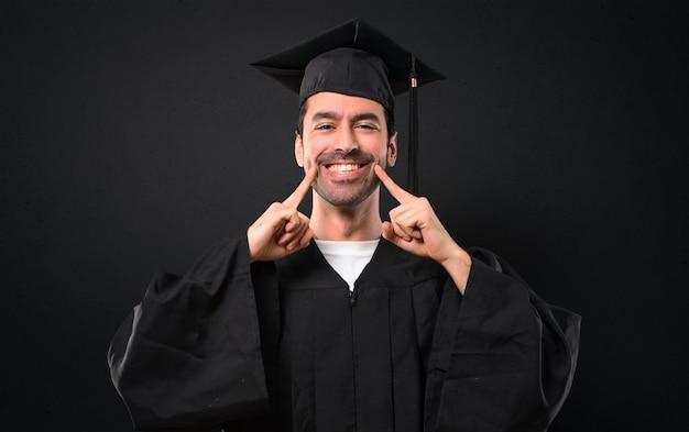 Mężczyzna w dniu jego ukończenia uniwersytet uśmiecha się z wyrażeniem szczęśliwy i przyjemny