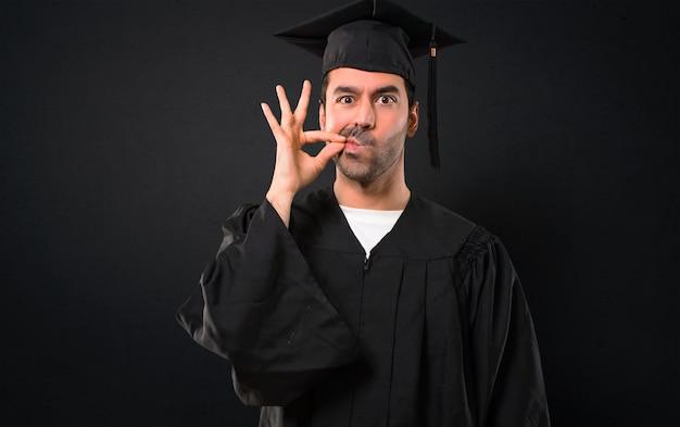Mężczyzna w dniu jego ukończenia uniwersytet wykazujące oznakę zamknięcia gestu usta i cisza