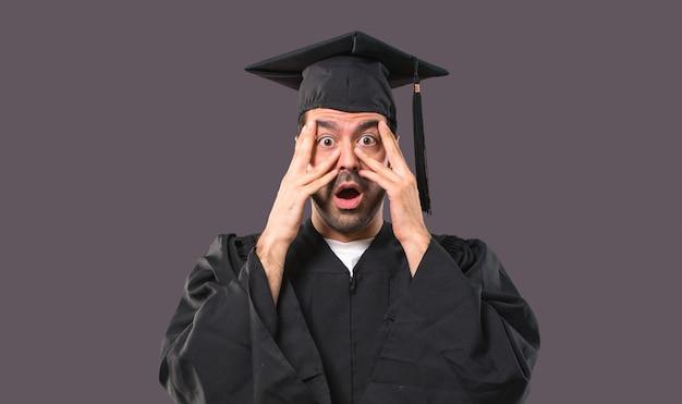 Mężczyzna w dniu jego ukończenia uniwersytet zaskoczony i obejmujące twarz rękami