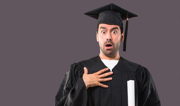 Mężczyzna w dniu ukończenia uniwersytetu zaskoczony i zszokowany, gdy patrzy w prawo