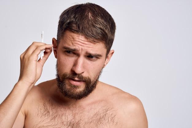 Mężczyzna w domu czyści uszy