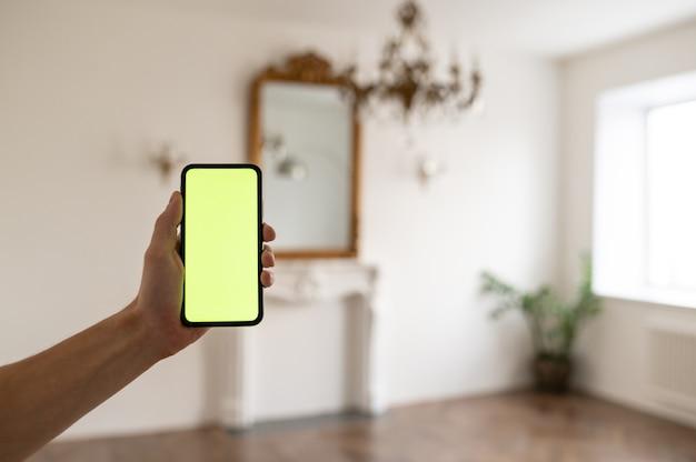 Mężczyzna w domu leżący na kanapie, używający smartfona z zielonym ekranem makiety, robiący swi...
