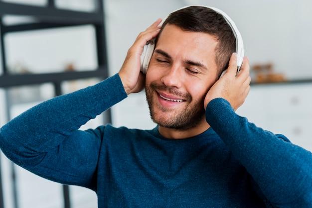 Mężczyzna w domu na kanapie ze słuchawkami