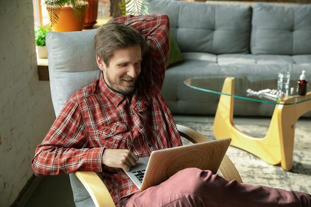 Mężczyzna w domu, oglądając wideo na laptopie