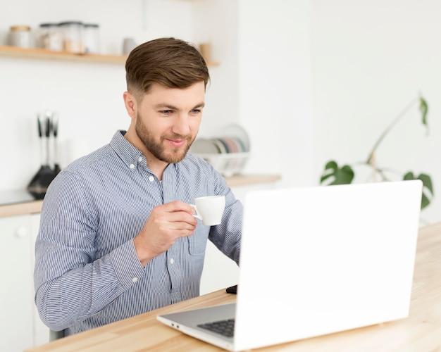 Mężczyzna w domu pracuje na laptopie