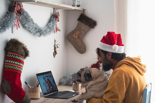 Mężczyzna w domu z psem cieszyć się świętami bożego narodzenia dzwoniąc do wideorozmowy wesoła kobieta - świąteczne czapki i dekoracje w domu - ludzie korzystają z połączenia internetowego online, aby pozostać razem