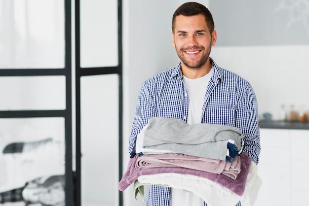 Mężczyzna w domu z wyprasowanymi ubraniami w rękach