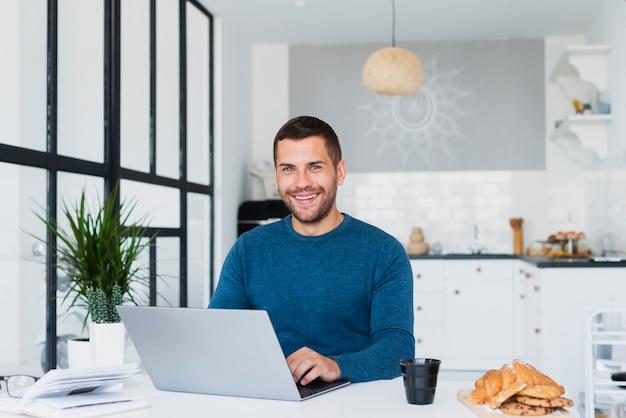 Mężczyzna w domu za pomocą makiety laptopa