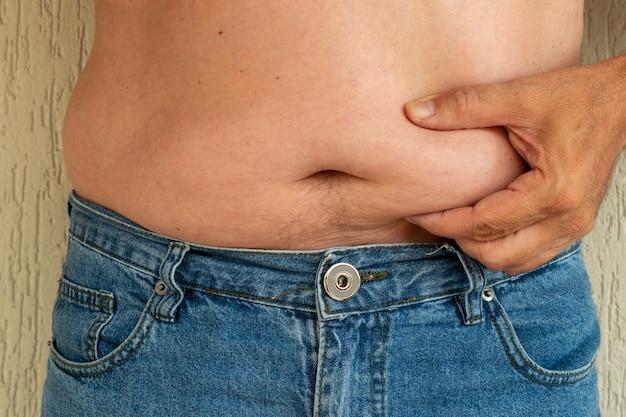 Mężczyzna w dżinsach, trzymając się za brzuch. tłuszcz brzuszny.