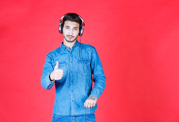 Mężczyzna w dżinsowej koszuli nosi słuchawki i pokazuje pozytywny znak ręki.