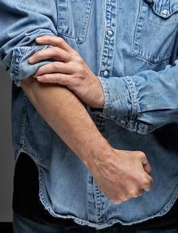 Mężczyzna w dżinsowej koszuli podwijającej rękawy